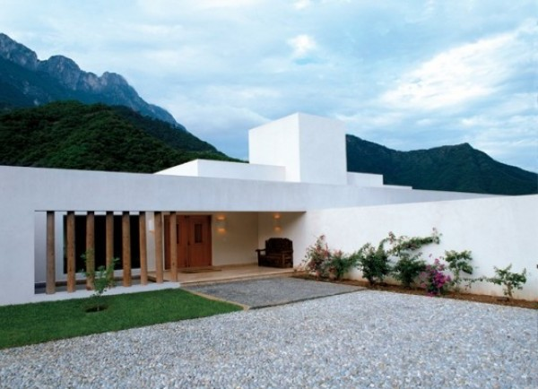 White Concrete House Surrounded By Greens And Blues Of